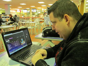 Photo - FILE - In this Nov. 21, 2013 file photo, Joseph Brennen of Ventnor NJ logs on to a Harrah's online casino on his laptop from a highway rest area in Egg Harbor Township NJ on  the first day of a test of Internet gambling in New Jersey. Online betting got off to a slow start in New Jersey, taking in $8.4 million over the last few weeks of 2013, but casino executives and Wall Street analysts expect it to pick up steam in 2014. (AP Photo/Wayne Parry, File)