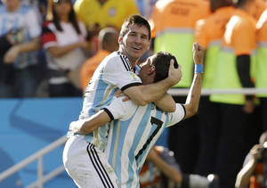 Photo - Argentina's Angel di Maria, right, and Lionel Messi celebrate after di Maria scored during the World Cup round of 16 soccer match between Argentina and Switzerland at the Itaquerao Stadium in Sao Paulo, Brazil, Tuesday, July 1, 2014. (AP Photo/Kirsty Wigglesworth)