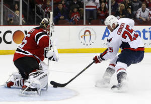 Photo - New Jersey Devils goalie Cory Schneider, left, blocks a shot by Washington Capitals left wing Jason Chimera during the first period of an NHL hockey game, Friday, April 4, 2014, in Newark, N.J. (AP Photo/Julio Cortez)