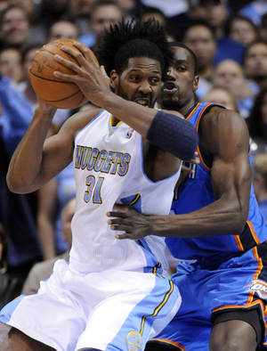 Photo - Denver Nuggets center Nene (31) from Brazil spins around Oklahoma City Thunder forward Serge Ibaka (9) from the Republic of Congo during the first half of game 3 of a first-round NBA basketball playoff series Saturday, April 23, 2011, in Denver. (AP Photo/Jack Dempsey)