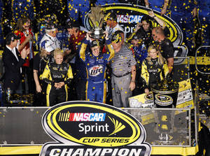 photo - Brad Keselowski, center, holds up his trophy after winning the NASCAR Sprint Cup Series championship following an auto race at Homestead-Miami Speedway, Sunday, Nov. 18, 2012, in Homestead, Fla. Keselowski clinched the title after fellow contender Jimmie Johnson pulled out of the season finale because of a parts failure. Jeff Gordon won the race. (AP Photo/Wilfredo Lee) ORG XMIT: FLWL104