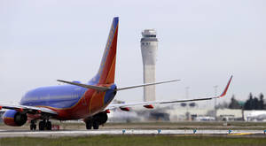 Photo - This photo taken April 23, 2013 shows a Southwest airlines jet waiting to depart in view of the air traffic control tower at Seattle-Tacoma International Airport in Seattle. With disgruntled passengers complaining about airline flight delays, Republican lawmakers and the airline industry pounced on the Obama administration. The glitch was invented by the White House for political reasons, they charged, and officials waited until the last minute to warn Congress and the airlines of the impending upheaval. (AP Photo/Elaine Thompson)