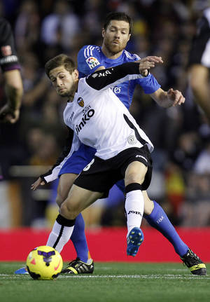 Photo - Real Madrid's  Xabi Alonso duels for the ball with Valencia's Fede Cartabia during their La Liga soccer match at the Mestalla stadium in Valencia, Spain, Sunday, Dec. 22, 2013. (AP Photo/Alberto Saiz)