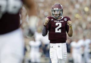 Photo - Texas A&M's Johnny Manziel (2) celebrates a touchdown by teammate Ben Malena during the fourth quarter of an NCAA college football game against Rice, Saturday,  Aug. 31, 2013, in College Station, Texas.  (AP Photo/Eric Gay)