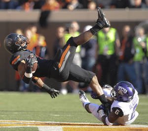 photo -   TCU safety Elisha Olabode, right, tackles Oklahoma State running back Joseph Randle, left, during the first half of an NCAA college football game in Stillwater, Okla., Saturday, Oct. 27, 2012. (AP Photo/Brody Schmidt)