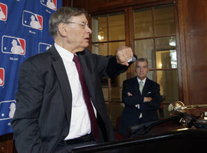 Photo - Major League Baseball Commissioner Bud Selig checks his watch before a news conference following baseball meetings at the Otesaga Hotel on Thursday, Aug. 15, 2013, in Cooperstown, N.Y. Atlanta Braves President John Schuerholz stands at right. (AP Photo/Mike Groll)