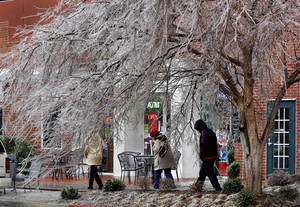 Photo - A winter storm moved through Oklahoma late Friday and left  scenes resembling a winter wonderland in the central part of the state, coating trees, cars, and buildings in ice. Three pedestrians in Bricktown walk beneath ice-covered trees on Sheridan Avenue on  Dec. 21, 2013. _Photo by Jim Beckel, The Oklahoman