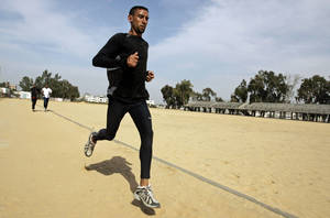 Photo - FILE - In this Saturday, April 5, 2008 file photo, Nader Masri exercises in Gaza City. On Tuesday, April 8, 2014 Israel's high court has upheld a decision by the military to prevent Nader Masri, 34, a Gaza Olympian, from leaving the coastal strip to participate in a marathon in the West Bank. Israel has severely restricted the movement of people and goods in and out of Gaza since the Islamic militant Hamas took control there in 2007. Tuesday's ruling ends hopes of 34-year-old Nader Masri to participate in Friday's marathon in biblical Bethlehem. Israel says only humanitarian hardship cases are allowed to leave Gaza. (AP Photo/Hatem Moussa/File)