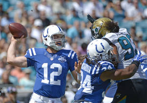 Photo - Indianapolis Colts quarterback Andrew Luck (12) throws a pass as running back Trent Richardson (34) blocks Jacksonville Jaguars defensive end Tyson Alualu (93) during the first half of an NFL football game in Jacksonville, Fla., Sunday, Sept. 29, 2013.(AP Photo/Phelan M. Ebenhack)