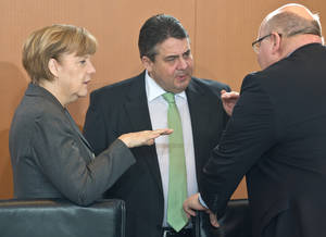 Photo - German Chancellor Angela Merkel, left, talks to Economy Minister and Vice Chancellor Sigmar Gabriel and her chief of staff Peter Altmaier, right, prior to the weekly cabinet meeting in the Chancellery in Berlin, Tuesday, April 8, 2014. (AP Photo/dpa, Tim Brakemeier)