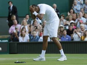 Photo - Nick Kyrgios of Australia holds his head after defeating Rafael Nadal of Spain in their men's singles match on Centre Court at the All England Lawn Tennis Championships in Wimbledon, London, Tuesday, July 1, 2014. (AP Photo/Ben Curtis)