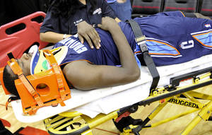 Photo - Charlotte Bobcats' Michael Kidd-Gilchrist is wheeled off the floor after a hard fall in the second half of an NBA basketball game against the Houston Rockets, Saturday, Feb. 2, 2013, in Houston. (AP Photo/Pat Sullivan)
