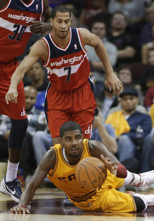 Photo -   Cleveland Cavaliers' Kyrie Irving grabs a loose ball in front of Washington Wizards' Jannero Pargo (7) during the third quarter of an NBA basketball game Tuesday, Oct. 30, 2012, in Cleveland. Trving scored 29 points to lead the Cavaliers to a 94-84 win in the season opener. (AP Photo/Mark Duncan)