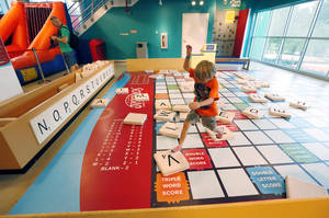 Photo - In this July 3, 2014 photograph, Maston Johnson, 5, from Tampa, Fla., leaps through the oversized Scrabble board after spelling out his name, at the Mississippi Children's Museum in Jackson, Miss. The interactive hands-on facility promotes literacy, health and nutrition, learning the state's heritage and exploration of its cultural arts and key economic industries in a fun setting. (AP Photo/Rogelio V. Solis)