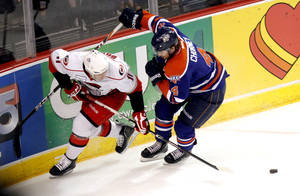 photo - Oklahoma City's Taylor Chorney and Charlotte's Zach Boychuk fight for control of a puck during the AHL hockey game between the Oklahoma City Barons and the Charlotte Checkers at the Cox Convention Center in Oklahoma City, Friday, Feb. 3, 2012. Photo by Sarah Phipps, The Oklahoman ORG XMIT: KOD