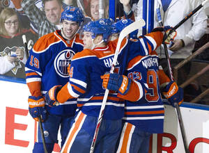 Photo - Edmonton Oilers' Justin Schultz (19), Jordan Eberle (14) and Taylor Hall (4) celebrate Ryan Nugent-Hopkins's (93) winning goal against the Pittsburgh Penguins in overtime NHL hockey action in Edmonton, Alberta, on Friday Jan. 10, 2014. (AP Photo/The Canadian Press, Jason Franson)