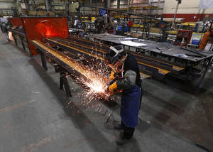 Photo - In this Thursday, Jan. 23, 2014 photo, Jesus Rodriguez grinds steel at the IDEAL Group in Detroit. The Institute for Supply Management reports on U.S. manufacturing activity in February on Monday, March 3, 2014.  (AP Photo/Paul Sancya)