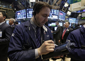 Photo - Trader Michael Mozian works on the floor of the New York Stock Exchange Tuesday, March 25, 2014.  Stocks are opening higher on Wall Street as the market shrugs off a two-day decline. (AP Photo/Richard Drew)