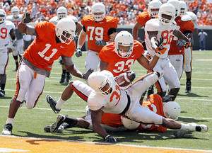 Photo - OSU's Jeremy Smith, bottom, rushes for a touchdown in front of Shaun Lewis, left, Andrew Smith, second from left, LeRon Furr, third from left, and Isaiah Anderson during the Orange-White Spring Game at Boone Pickens Stadium in Stillwater on Saturday. Photo by Nate Billings, The Oklahoman