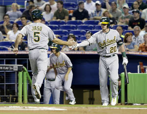 Photo - Oakland Athletics' John Jaso (5) is congratulated by Josh Donaldson (20) after Jaso and Coco Crisp (not shown) scored on a single by Brandon Moss during the first inning of a baseball game against the Miami Marlins, Saturday, June 28, 2014, in Miami. (AP Photo/Wilfredo Lee)