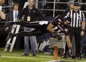 Photo - Northern Illinois wide receiver Juwan Brescacin dives into the endzone with a 15-yard touchdown reception against Utah State in the fourth quarter of the Poinsettia Bowl NCAA college football game Thursday, Dec. 26, 2013, in San Diego. (AP Photo/Lenny Ignelzi)