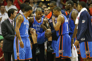 photo - Oklahoma City Thunder point guard Eric Maynor is carried off the court by his teammates after tearing his ACL vs. Houston on Jan. 7. AP PHOTO