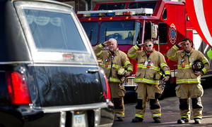 Photo - Firefighters salute as a hearse passes for the funeral procession to the burial of 7-year-old Sandy Hook Elementary School shooting victim Daniel Gerard Barden, Wednesday, Dec. 19, 2012, in Newtown, Conn. Barden was killed when Adam Lanza walked into Sandy Hook Elementary School in Newtown, Conn., Dec. 14, and opened fire, killing 26 people, including 20 children, before killing himself. (AP Photo/David Goldman)