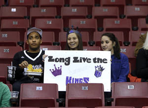 Photo - Sacramento Kings fan Jericka Hale, center, shows her support for her team with Bryan Oliver, left, and Chelsea Williams during an NBA basketball game against the Phoenix Suns in Sacramento, Calif., Wednesday, Jan. 23, 2013. The Maloof family, majority owners of the team, have announced they have signed an agreement to sell the Kings to a Seattle Group led by investor Chris Hansen. (AP Photo/Rich Pedroncelli)