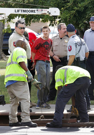 photo - Police handcuff a man after his removal from a storm drain at SW 78 Street and May Avenue. Photo by Paul B. Southerland, The Oklahoman <strong>PAUL B. SOUTHERLAND - PAUL B. SOUTHERLAND</strong>