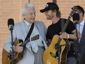Photo -   Country music star Dierks Bentley gets a hug from bluegrass star Del McCoury, left, after they performed at a free, outdoor concert in downtown Nashville, Tenn., on Tuesday, Sept. 27, 2011, during the week-long International Bluegrass Music Association celebration. (AP Photo/Mark Humphrey)