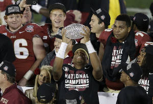 Photo - Florida State's Jameis Winston celebrates with The Coaches' Trophy after the NCAA BCS National Championship college football game against Auburn Monday, Jan. 6, 2014, in Pasadena, Calif. Florida State won 34-31. (AP Photo/Gregory Bull)