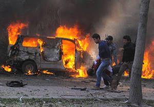 photo - This photo released by the Syrian official news agency SANA, shows Syrian security agents carrying a body following a huge explosion that shook central Damascus, Syria, Thursday, Feb. 21, 2013. A car bomb shook central Damascus on Thursday, exploding near the headquarters of the ruling Baath party and the Russian Embassy, eyewitnesses and opposition activists said. (AP Photo/SANA)