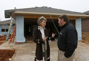 photo - Ann Felton Gilliland, CEO of Central Oklahoma Habitat for Humanity, and Jay Kreft, plant manager for Malarkey Roofing Products, talk at a Habitat house on SE 26, the first of 40 to be roofed this year with materials donated by Malarkey. Photo by NATE BILLINGS, The Oklahoman