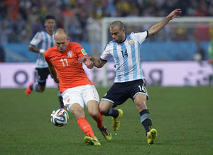 Photo - Netherlands' Arjen Robben, left, is challenged by Argentina's Javier Mascherano during the World Cup semifinal soccer match between the Netherlands and Argentina at the Itaquerao Stadium in Sao Paulo Brazil, Wednesday, July 9, 2014. (AP Photo/Manu Fernandez)