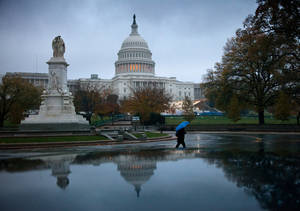 photo - FILE - In this Nov. 13, 2012 file photo, a man walks in front of the Capitol in Washington. The debate in Washington over taxes and spending is likely to continue damaging the fragile economy well into 2013. The political standoff has already taken an economic toll, creating uncertainty about the future and discouraging consumers from spending and businesses from hiring and investing. (AP Photo/J. Scott Applewhite, File)
