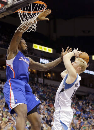 Photo - Minnesota Timberwolves forward Chase Budinger, right, is fouled by Los Angeles Clippers center DeAndre Jordan, left, during the fourth quarter of an NBA basketball game in Minneapolis, Monday, March 31, 2014. The Clippers won 114-104. (AP Photo/Ann Heisenfelt)