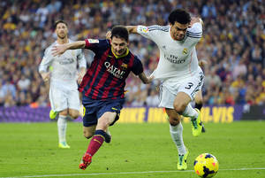 Photo - Real Madrid's Pepe, right, duels for the ball against FC Barcelona's Lionel Messi during the Spanish La Liga soccer match against FC Barcelona at the Camp Nou stadium in Barcelona, Spain, Saturday, Oct. 26, 2013. (AP Photo/Manu Fernandez)