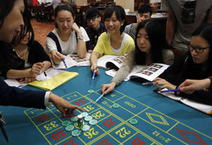 photo -   In this Nov. 25, 2012 photo, a gambling school students practice on a table in Macau, China. The students sitting around the roulette table are getting schooled on how to quickly calculate payoffs for the casino game by glancing at how the bets are placed. Elsewhere in the room, the biggest mock casino in Asia, other students are playing practice hands of blackjack or learning how to run a craps table. (AP Photo/Vincent Yu)
