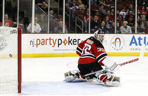Photo - A shot by New York Islanders' Anders Lee enters the net of New Jersey Devils goalie Martin Brodeur (30) for a goal during the first period of an NHL hockey game on Friday, April 11, 2014, in Newark, N.J. (AP Photo/Julio Cortez)