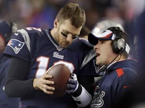 Photo - FILE - In this Nov. 3, 2013, file photo, New England Patriots offensive coordinator Josh McDaniels, right, talks to quarterback Tom Brady during the fourth quarter of an NFL football game against the Pittsburgh Steelers in Foxborough, Mass. No name stirs up quite as much angst and anger around Denver as McDaniels. The former Broncos coach, now offensive coordinator for the Patriots, left havoc in the wake of his two-year stint in Denver, and has a chance to leave another scar when the Patriots meet the Broncos in the AFC championship game on Sunday. (AP Photo/Steven Senne, File)