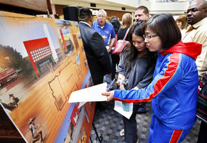 Photo - Current tenants Helen Lam and Collette Kim look at plans for the new Crossroads Mall, which will be renamed Plaza Mayor at the Crossroads. Photos by Steve Sisney, The Oklahoman