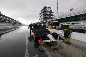 Photo - The crew of Tony Kanaan, of Brazil, pushes the car back to the garage area as rain halted practice for Indianapolis 500 IndyCar auto race at the Indianapolis Motor Speedway in Indianapolis, Friday, May 16, 2014. (AP Photo/Darron Cummings)