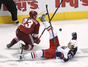 photo - Columbus Blue Jackets' Jared Boll (40) and Phoenix Coyotes' Oliver Ekman-Larsson (23) battle for the puck during the second period of an NHL hockey game, Saturday, Feb. 16, 2013, in Glendale, Ariz. (AP Photo/Matt York)
