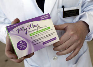 Photo - In this May 2, 2013 photo, pharmacist Simon Gorelikov holds a generic emergency contraceptive, also called the morning-after pill, at the Health First Pharmacy in Boston. (AP Photo/Elise Amendola, File)