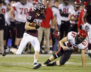 Photo - Edmond Memorial's Hunter Dawson (10) gets past Derek Gavin (87) of Mustang on the way to returning an interception for a touchdown all the way from Edmond Memorial's own end zone in the second quarter during the Class 6A high school football playoff game between Mustang and Edmond Memorial at Wantland Stadium in Edmond, Okla., Friday, Nov. 13, 2009. Photo by Nate Billings, The Oklahoman
