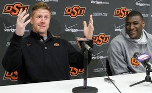 Photo - Oklahoma State quarterback Brandon Weeden, left, gestures as he announces that both he and All-America receiver Justin Blackmon, right, will return for another season, during a news conference in Stillwater, Okla.,  Wednesday, Jan. 12, 2011. (AP Photo/Sue Ogrocki)