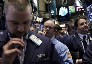 Photo - FILE - In this April 11, 2014 file photo, traders work on the floor of the New York Stock Exchange, Friday, April 11, 2014. World stock markets were mostly lower Tuesday, April 15, 2014, as Ukraine tensions continued to bubble and jitters about China's economy resurfaced. (AP Photo/Richard Drew, File)