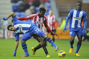 photo - Wigan Athletic's Jean Beausejour, left, of Chile,  battles for the ball with Sunderland's French player Alfred N'Diaye during their English Premier League match at the DW Stadium, Wigan, Saturday Jan. 19, 2013. (AP Photo / Martin Rickett, PA) UNITED KINGDOM OUT - NO SALES - NO ARCHIVES