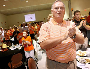 Photo - Oklahoma State defensive coordinator Bill Young joins Cowboys fans during the fight song at the OSU  Caravan in Enid on Monday. PHOTO BY JOHN CLANTON, THE OKLAHOMAN