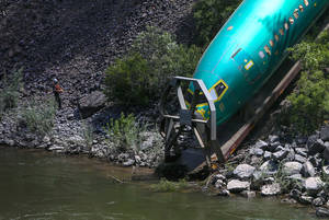 Photo -  Work crews remove a Boeing 737 fuselage that plunged into the Clark Fork River east of Superior, Mont., on Monday. Boeing is deciding what to do with the six new commercial airplane bodies that fell off a train in a derailment in western Montana, including three that slid down a steep riverbank, a company spokeswoman said. AP Photo/seattlepi.com, Joshua Trujillo  <strong>Joshua Trujillo</strong>